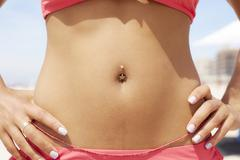 Close up of mixed race woman's pierced bellybutton Stock Photos