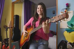 Hispanic girl playing guitar Stock Photos