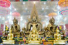 Seated buddha images in attitude of subduing mara and meditation with arch fr - stock photo