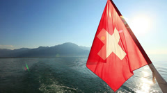 Swiss flag in foreground on lake Geneva Stock Footage