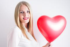 woman holding a red heart balloon - stock photo