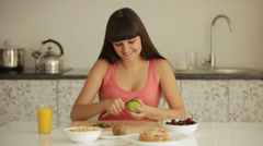 Young woman sitting at kitchen table and peeling kiwi fruit Stock Footage