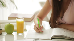 Student girl sitting at table writing in notebook and smiling at camera Stock Footage