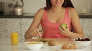Stock Video Footage of Charming girl sitting at kitchen table peeling and eating kiwi fruit