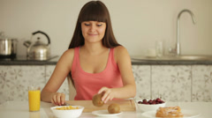 Cheerful girl sitting at kitchen table and peeling kiwi fruit Stock Footage