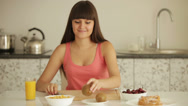 Stock Video Footage of Cheerful girl sitting at kitchen table and peeling kiwi fruit