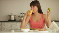 Stock Video Footage of Cute girl sitting at kitchen table eating kiwi and drinking juice
