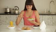 Stock Video Footage of Pretty girl sitting at kitchen table and eating sliced fruit