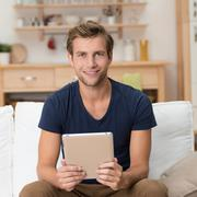 casual young man holding a tablet-pc - stock photo
