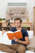 Stock Photo of young man relaxing reading a book