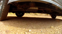 Underside of a car on dirt road Stock Footage