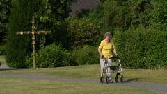 retiree pensioner walk with rollator in park 11074 - stock footage