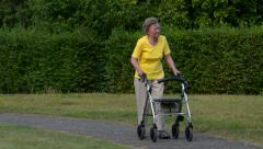 Pensioner walk and watch with rollator 11082 Stock Footage