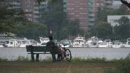 Stock Video Footage of Biker relaxing on St Charles river
