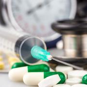 syringe, different pills, stethoscope and sphygmomanometer - stock photo