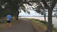 Joggers and walkers on the Charles river esplanade Stock Footage