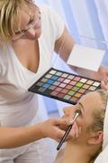 Young woman having beautiful make up applied Stock Photos