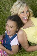 young african american girl and blond woman family joke - stock photo