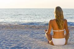 beautiful woman sat in tranquility on a deserted beach - stock photo