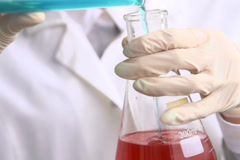 Scientist pouring chemicals in erlenmeyer flask NTSC Stock Footage