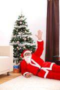 Santa claus laying on floor in front of christmas tree - stock photo