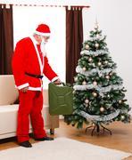 santa claus bringing gas as present - stock photo