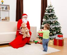 Little boy taking out toys from Santa's bag - stock photo