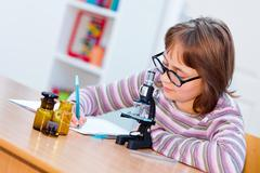 Teen science girl with microscope - stock photo