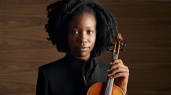 Portrait of classical musician holding violin African American woman Stock Footage