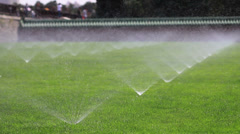 Irrigating grass with water sprinkler Stock Footage