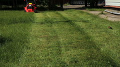 Garden worker cutting overgrown grass with lawn mower weeding machine Stock Footage