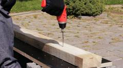 Carpenter using a screw gun to fasten screw into a wood board. Stock Footage