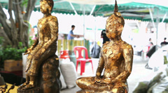 A buddha statues with gold flakes waving in the temple - stock footage