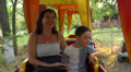 boy with mum on the carousel in an amusement park 3 HD Footage