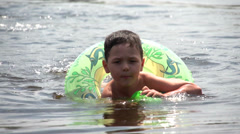 Baby floating in rubber ring in the sea Stock Footage