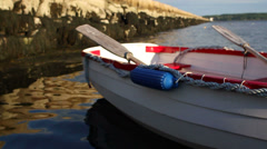Row boat tied to dock next to breakwater - stock footage