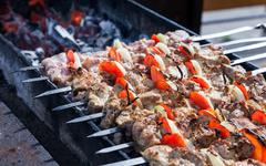 Juicy slices of meat with sauce prepare on fire (shish kebab) Stock Photos