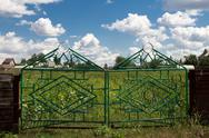 Iron fence and a blue sky with clouds Stock Photos