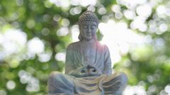 Bronze Buddha in Traditional Sitting Meditation Pose on Green Bokeh Background Stock Footage