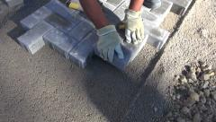Mason worker making sidewalk pavement with stone bricks Stock Footage