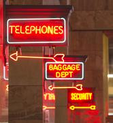 Stock Photo of red neon sign indoor depot signage arrow points baggage telephones