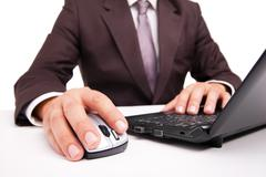 Computer mouse in hand businessman on white - stock photo