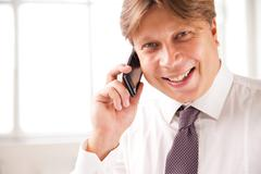 Laughing businessman on the phone in his office - stock photo