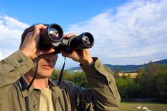 Man with binoculars - stock photo