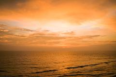 Tranquil sunset over seascape - stock photo