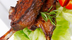 Meat plate: roast ribs on white with tomatoes Stock Footage