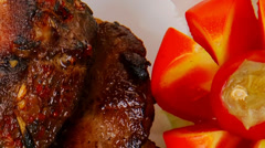 meat plate: roast ribs on white with tomatoes - stock footage