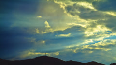 Cross on Distant Hill with Clouds and Sunbeams Stock Footage
