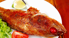 Savory on wood: fried fish served with tomatoes Stock Footage