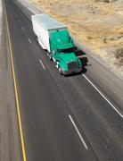 Over the road transport semi truck hauling cargo containier freeway Stock Photos